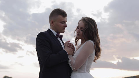 Groom with bride. Sky background. Wedding couple. Sunset. Happy newlyweds Live Action