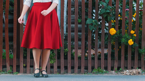 A young woman in long red skirt dancing by the fence on the street in the Live Action