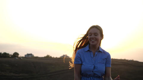 Happy young feminine girl runs on a background of sunny sunset. Her long silky Live Action