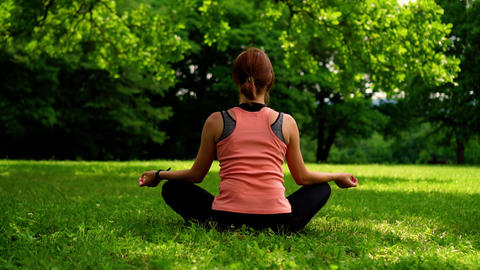 girl sitting in the lotus position on the grass in the park Footage