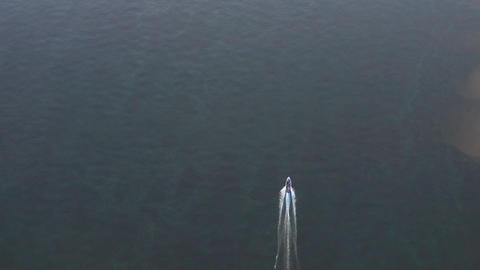 Drone aerial view boat sailing in blue sea water. Motor boat floating on transparent lake water. Top Live Action