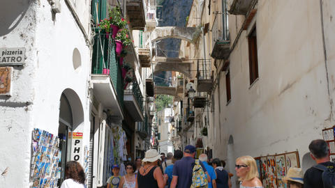 People near the shop with postcards and Amalfi architecture Live Action