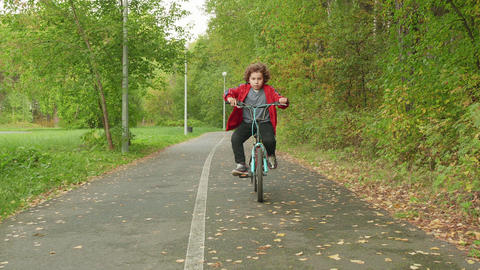 Cute boy bicyclist riding on bicycle in summer park. Portrait curly boy riding Live Action
