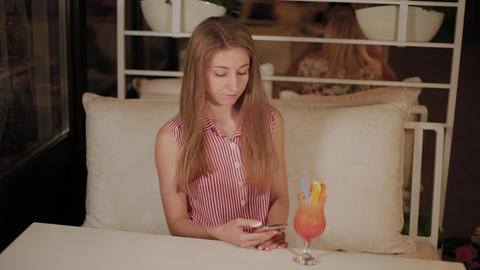 Beautiful girl with a beautiful fresh bright bright evening cocktail in a cafe Footage