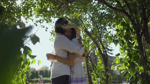 Happy young couple hugging in the park or garden. Leisure outdoors, connecting Footage