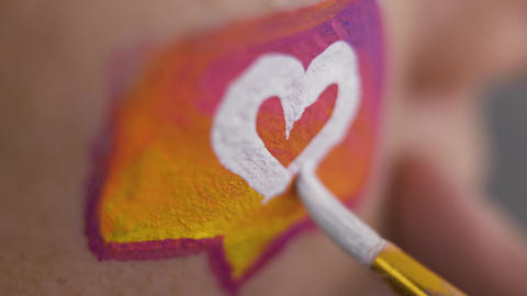 Extreme close-up of the artist painting small white heart on the human body Live Action