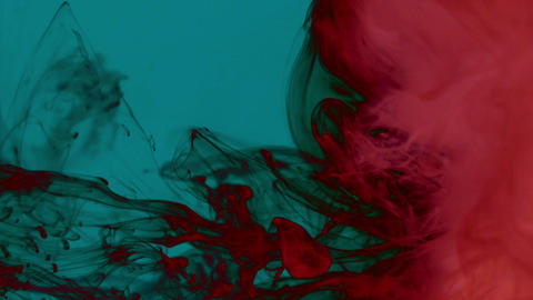 Bright red smoke on a dark turquoise background moving from left Footage