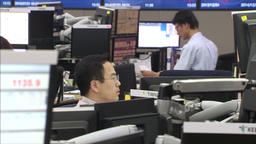 CHINESE TRADER DEALING IN STOCK MARKET BUYING AND LOOKING AT COMPUTER SCREENS Footage