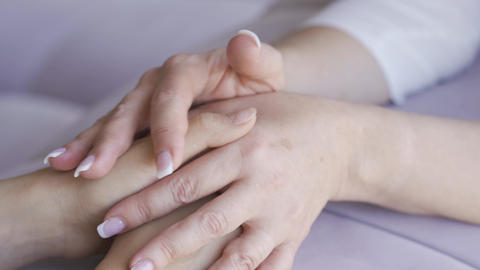 One women holding hands of other woman close-up. Mother calming her daughter Footage