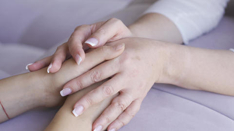 Two women holding hands close-up. Mother calming her daughter. Friendly Live Action