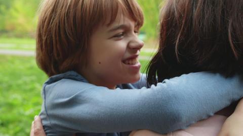 Close up face smiling boy teenager hugging mom outdoor. Portrait teenager boy Footage
