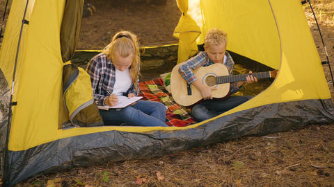 Teenager boy with guitar sitting in camping tent. Young girl teenager painting Footage
