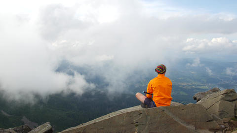 Hiker in a bright jacket on top. A tourist looks at the clouds and the view from Footage