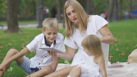 Cute caucasian woman and two children spending time outdoors. The woman showing Footage