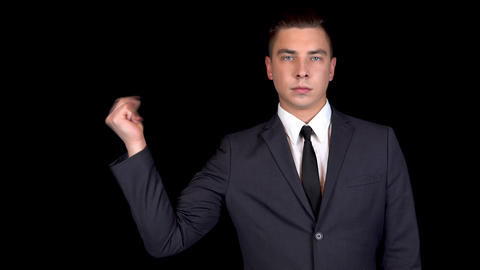 Young businessman clicks his fingers. Man in a black suit on a black background Live Action