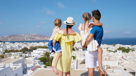 Family in Europe. Parents and kids background the old town in Mykonos island Live Action