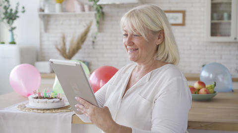 Positive mature woman scrolling tablet screen and smiling while standing in the Footage