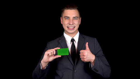 Young businessman presents a bank green card and shows like with his hand Live Action