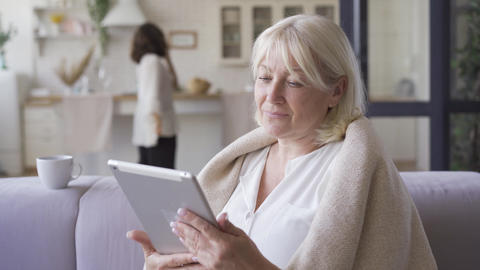 Positive mature woman covered in blanket sitting on the sofa watching photos on Footage