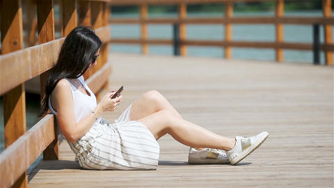 Cute woman is reading text message on mobile phone while sitting in the park Live Action