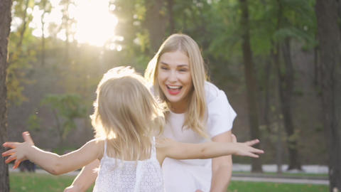 Back view of little blond girl running towards her mother in the sunshine Live Action