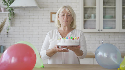 Positive senior woman showing a cake prepared for her child or grandchild Footage