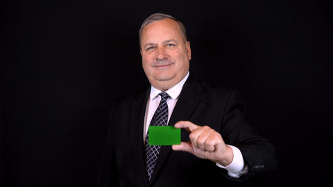 Old businessman in a suit holds a bank card in his hand. Chromakey green card Live Action