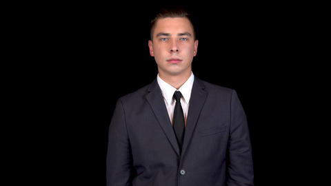 Young businessman shakes his head denying. Man in a black suit on a black Footage