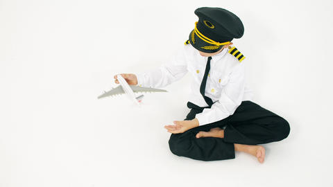 Boy wearing pilot's uniform plays with toy commercial airplane Live Action