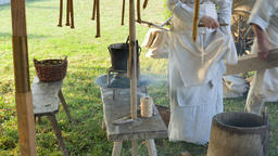 Life in medieval village. Woman is polishing handmade, beeswax candles Live Action