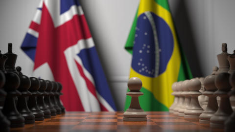 Chess game against flags of Great Britain and Brazil. Political competition Live Action