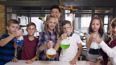 Portrait shot of Korean male teacher with group of six cheerful young caucasian Live Action
