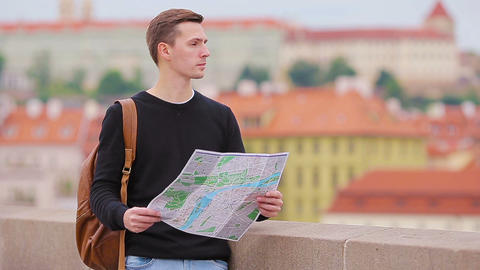 Man tourist with a city map and backpack in Europe. Caucasian boy looking with Footage