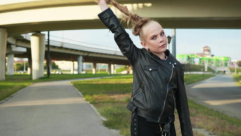 Young girl in black leather jacket holding hair tail on cityscape background Footage