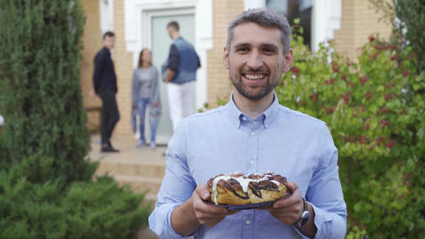 Smiling caucasian man standing with a cake and smiling. A group of people in the Live Action