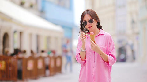 Young girl eating ice cream cone outdoors. Summer concept - woman with sweet ice Footage