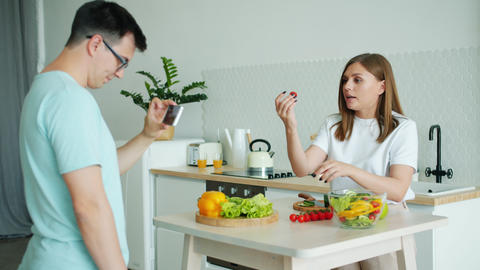 Girl cooking salad talking showing thumbs-up while guy recording video for vlog Live Action