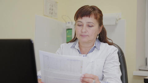 An elderly woman doctor takes a test result from a printer and examines it Live Action