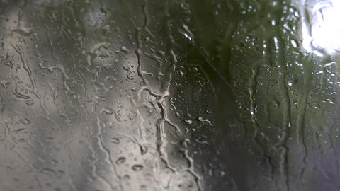 Raindrops on the glass. Drops flow down the glass closeup. 4k Live Action