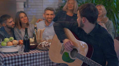 Young caucasian man playing guitar entertaining company of friends. People Live Action