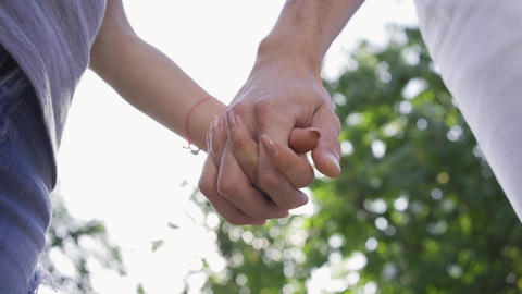 Close-up of man and woman holding hands. Tender relationship. Young couple Live Action