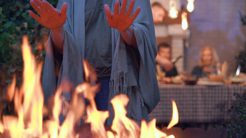 Close-up a person warming hands near the fire fire. Company of caucasian people Live Action
