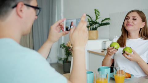 Slow motion of lady posing with apples when guy taking photo with smartphone Footage