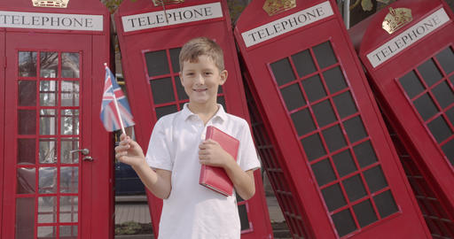 Slow motion portrait of cute boy waving British flag standing outdoors alone Footage