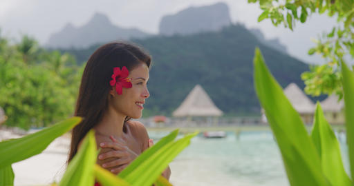 Woman wellness spa skincare Asian natural beauty on tropical beach in Tahiti Live Action