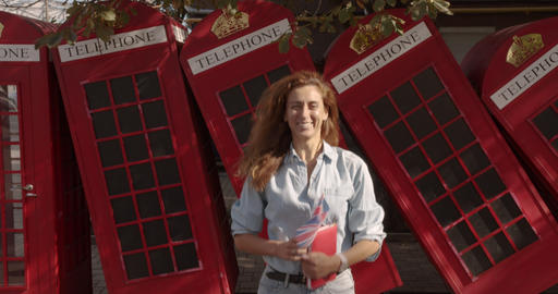 A woman holds a British flag and a book and bounces with them. Joy fun Footage