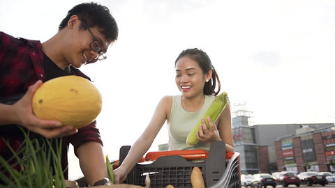 Cute cheerful asian couple puts into packets purchased food from the shopping Live Action