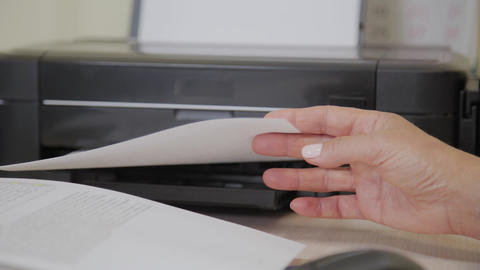 Elderly doctor woman takes out the result of the study from the printer Live Action