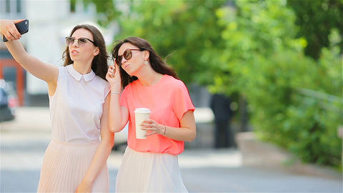 Two young girls taking selfie with smart phone outdoors. Two women after Live Action