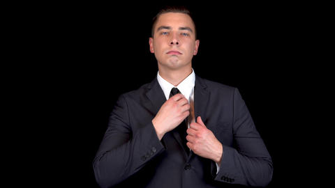 Young businessman straightens his suit. Man in a black suit on a black Live Action